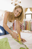 Fashion Designer Cutting Out Pattern From Fabric In Studio royalty free stock images