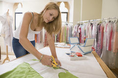 Fashion Designer Cutting Out Pattern From Fabric In Studio royalty free stock photo