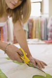 Fashion Designer Cutting Out Pattern From Fabric In Studio stock photo