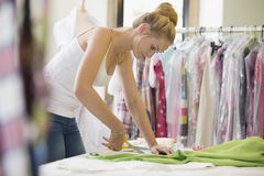 Fashion Designer Cutting Out Pattern From Fabric In Studio royalty free stock image