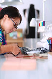 Fashion designer cutting textile next to a sewing Royalty Free Stock Photos