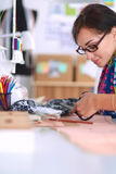 Fashion designer cutting textile next to a sewing Stock Image