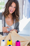 Fashion designer cutting textile next to a sewing machine. And smiling to the camera royalty free stock image