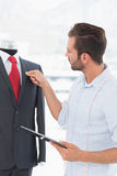 Fashion designer with digital tablet looking at suit on dummy. Concentrated young male fashion designer with digital tablet looking at suit on dummy in the Royalty Free Stock Photo