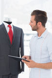 Fashion designer with digital tablet looking at suit on dummy. Concentrated young male fashion designer with digital tablet looking at suit on dummy in the Royalty Free Stock Photos