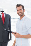 Fashion designer with digital tablet by suit on dummy Royalty Free Stock Photo