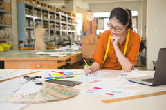 Fashion designer drawing design sketch. Authentic image of asian fashion woman designer drawing design sketch working in her manufacturing office studio Stock Photography