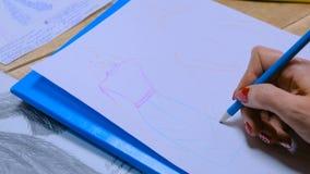 Fashion designer drawing design sketch. Close up shot - hands of professional tailor, designer drawing fashion sketch at atelier, studio. Dressmaking, creativity stock image