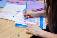 Fashion designer drawing design sketch. Close up shot - hands of professional tailor, designer drawing fashion sketch at atelier, studio. Dressmaking, creativity stock photography