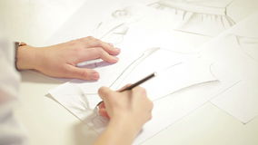 Fashion designer drawing sketches for clothes in atelier.