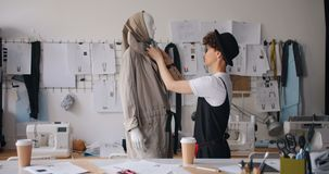 Fashion designer dressing mannequin checking handmade gadment working alone. Fashion designer tredny hipster is dressing mannequin checking handmade gadment stock video footage