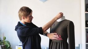 Fashion designer with dummy making dress at studio stock video
