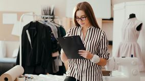 A fashion designer girl makes a sketch in a paper tablet and looks at the camera with a serious face. stock footage