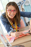 Fashion designer with glasses cutting fabric Stock Photos
