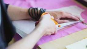 Fashion designer hands cutting cloth with scissors