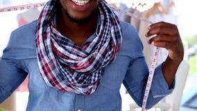 Fashion designer hanging a measuring tape around his neck stock video footage