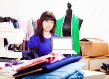 Fashion Designer In Her Studio. A female fashion designer is working on a new piece of clothing in her somewhat chaotic studio. in this shot, she is holding a stock photography