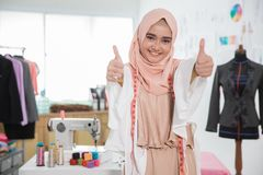 Fashion designer in her workshop showing thumb up. Portrait of young attractive muslim woman fashion designer in her workshop showing thumb up Stock Photography
