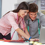 Fashion designer with laptop. Two happy fashion designer browing the internet with a laptop computer royalty free stock image