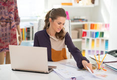 Fashion designer with laptop working in office Stock Image
