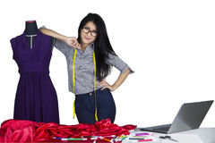 Fashion designer leans on mannequin royalty free stock photo
