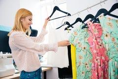 Fashion designer looking on dresses Royalty Free Stock Photos