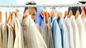 Fashion designer looking through her clothing rail. In her studio stock video footage