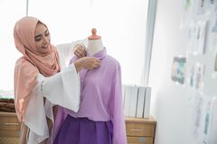 Fashion designer make a clothing. Portrait of attractive fashion designer create a clothing in her workshop Stock Images