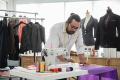 Fashion designer make a suit. Portrait of busy male fashion designer make a suit in his workshop Royalty Free Stock Photos