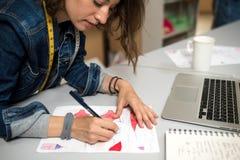 Fashion designer making sketch. Woman, designer clothes, making sketch of underwear in workshop Stock Photos
