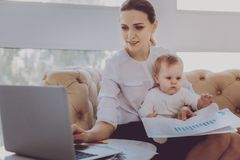 Fashion designer on maternity leave checking her e-mail while holding baby. Maternity leave. Fashion designer on maternity leave feeling motivated checking her e stock photos