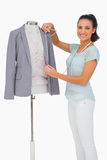 Fashion designer measuring blazer lapel on mannequin and smiling. On white background stock photography