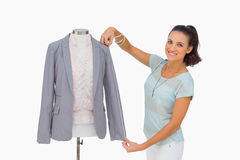 Fashion designer measuring blazer sleeve on mannequin and smiling Stock Photo