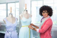 Fashion designer measuring dummy waist Stock Image