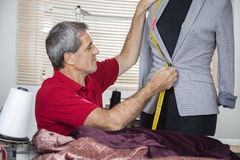 Fashion Designer Measuring Suit On Mannequin. Mature male fashion designer measuring suit on mannequin at sewing factory Stock Image