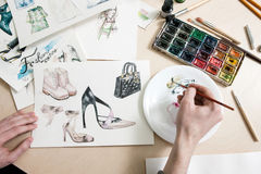 Fashion designer mixes colours of paint. In process of drawing fashion sketches of footwear and clothing stock photo