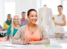 Fashion designer with notebook over studio. Education, clothing and tailoring concept - smiling african american female student or fashion designer with notebook stock photography