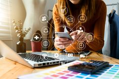Fashion designer Online Shopping payments concept. Fashion designer woman talking smart phone and using laptop with digital tablet computer in modern studio in royalty free stock photo