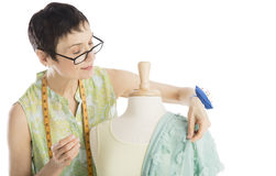 Fashion Designer Pinning Clothes To Mannequin. Female fashion designer pinning clothes to mannequin against white background royalty free stock photography