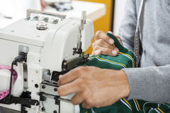 Fashion Designer Sewing Fabric At Workbench. Cropped image of male fashion designer sewing fabric at workbench in factory Stock Photo