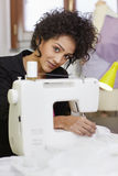 Fashion designer with sewing machine Stock Image