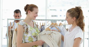 Fashion designer showing a dress to a model stock footage