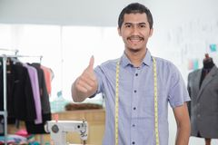 Fashion designer showing thumb up to camera. In his workshop Royalty Free Stock Photography