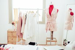 Fashion designer showroom studio workshop background with new collection of pink pastel female clothing design. Tailor and sewing