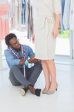 Fashion designer sitting on the floor adjusting dress Stock Photo