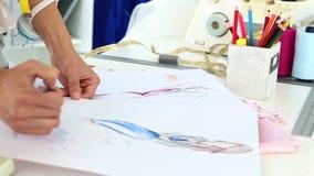 Fashion designer sketching a blue dress design stock video footage
