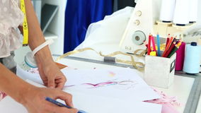 Fashion designer sketching a dress design stock footage