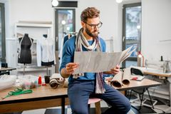 Fashion designer at the studio. Portrait of a handsome fashion designer sitting with clothing sketches at the studio full of tailoring tools and clothes stock images