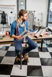 Fashion designer at the studio. Portrait of a handsome fashion designer sitting with clothing sketches at the studio full of tailoring tools and clothes Stock Image