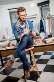 Fashion designer at the studio. Portrait of a handsome fashion designer sitting with clothing sketches at the studio full of tailoring tools and clothes Stock Photo